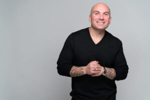 A photo of Henry Kaminski Jr is captured. He has spent the last 14 years helping entrepreneurs monetize their expertise and design their online presence. Henry speaks with Sam Carvalho on the Marketing A Practice Podcast.