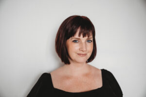 A photo of Dana Robertson is captured. She is a value based branding expert and co-owner of Pennant Creatives. Dana is featured on Grow a Group Practice, a therapist podcast.